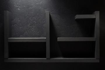 wooden shelf on black wall