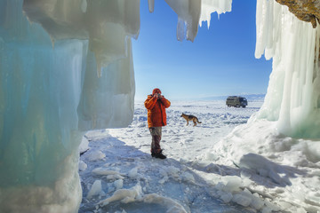 Male tourist photographer with dog near the ice grotto Olkhon Island on Lake Baika