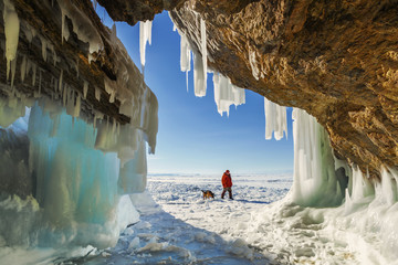 Male tourist with a dog near the ice grotto Olkhon Island on Lake Baikal