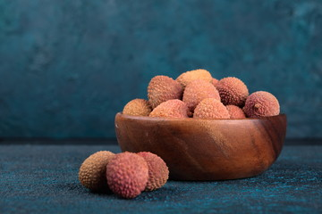 Lychee in a wooden bowl on a blue cement background