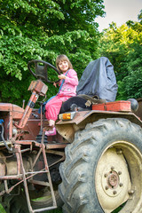 Girls pretending to drive a tractor on a sunny farm