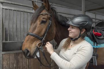 Junge Frau schließt den Backenriemen am Zaumzeug ihres Pferdes