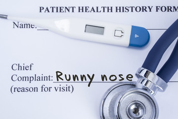 Chief complaint runny nose. Paper patient health history form, on which is written the complaint runny nose as the main reason for visit to the doctor, with a thermometer and stethoscope