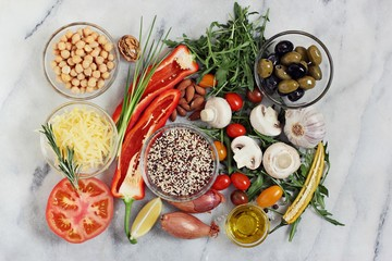 Healthy cooking concept ingredients with quinoa,chick pea, fresh vegetables and mushrooms overhead of murble cutting board