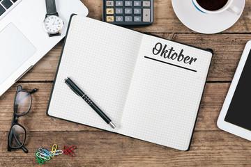 Oktober (German October) month name on paper note pad at office desk