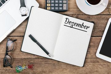 Dezember (German December) month name on paper note pad at office desk