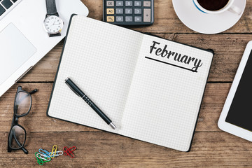 February; English month name on paper note pad at office desk