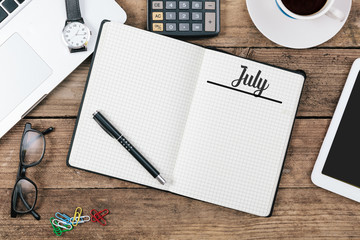 July, English month name on paper note pad at office desk