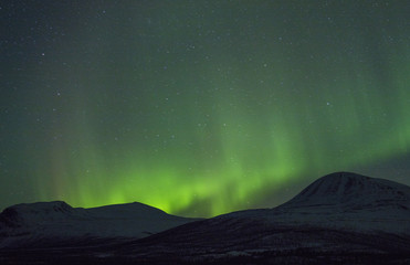 green northen lights above mountains in Sweden