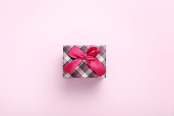 Gift box with ribbon on pink background