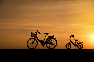 Silhouette of vintage bicycles on the road with the sunset background.