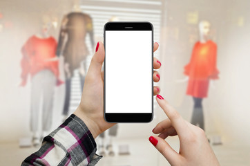 Women in boutique holding smartphone in hands with blank display, shopping online concept. Maneken dolls in boutique window in background