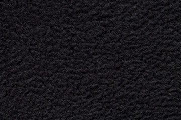 Black suede fabric closeup. Velvet texture.
