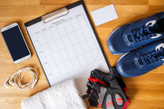Personal workout plan with sneakers, smartphone and other fitness stuff. Top view image