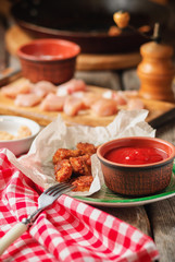 homemade fresh crunchy chicken nuggets, spicy tomato chili sauce and ingredients on rustic wooden table. close up and selective focus. shallow depth of field