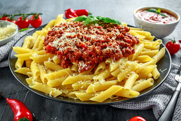 Hot Penne pasta bolognese with parmesan cheese, basil, Garlic, tomatoes, chili on plate.