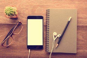 Smartphone with white screen and Note book On Wooden Table With Copyspace