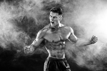 Strong bodybuilder man with perfect body- abs, shoulders, biceps, triceps, chest posing in studio smoke background