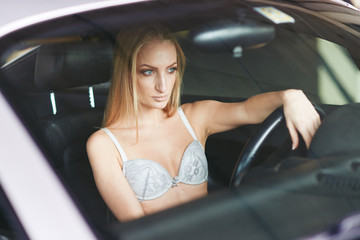 sexy young girl posing Topless in the car located in the Parking lot