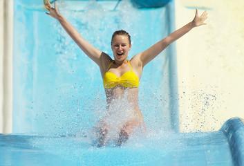 Woman sliding down on water-slide in aqua park.