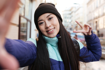 Asian woman in warm clothes making selfie