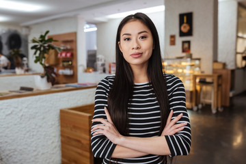 Asian woman with crossed arms in cafeteria