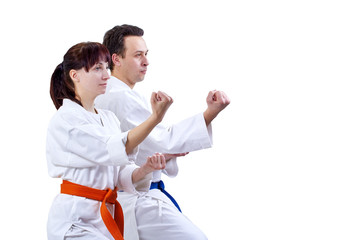 Man and woman in karategi stand in the rack karate