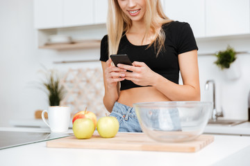 Cropped image of woman using smartphone on kitchen