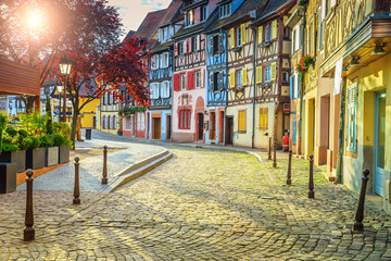 Colorful medieval half-timbered facades with paved road in Colmar