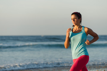 Woman running at the beach. Fitness female runner training and exercising on summer against the sea.