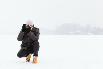 Young man taking a photo on the frozen lake in winter time