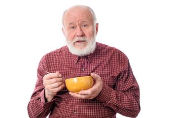 Senior man eating from oragne bowl , isolated on white