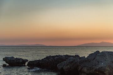 Evening on orange sunset on the sea coast in the summer among the rocks.