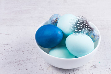 Plate with painted dark and light blue eggs on wooden table desktop