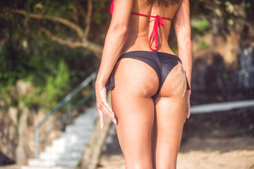 Sporty female butt in with two sand hand prints. Cropped image of young woman standing  her back turned to camera wearing bikini  blur natural landscape in background