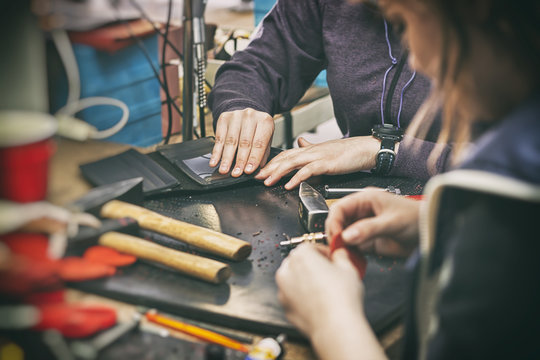 Two young womans work  with leather