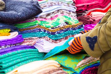 eine Frau prüft die Qualität von textilen Stoffen auf einem Markt