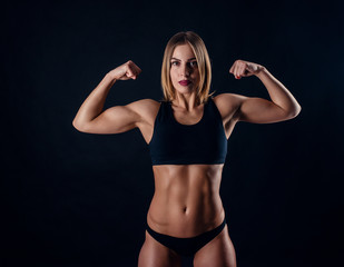 Sporty girl with great muscles in black sportswear. Tanned young athletic woman. A great sport female body. Muscular build female after workout.