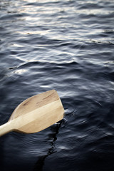 closeup of a canoe paddle rowing on a lake
