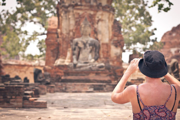 People take photo buddha ayutthaya thailand.