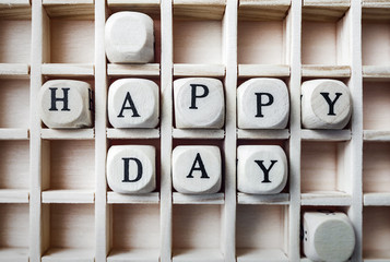 Message happy day made with building wooden blocks / Composition of the words happy day with wooden cubes in square box
