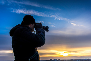 Photographer takes shot of sunset at background of clourful dramatic sky