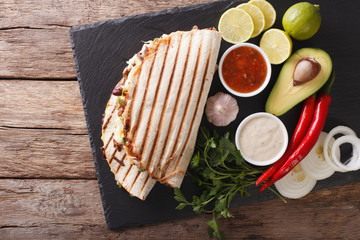 Mexican food: Quesadillas with beef, beans, avocado and cheese close-up. horizontal top view