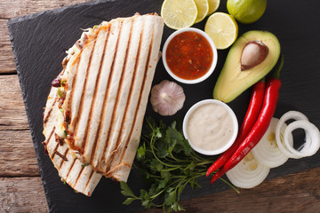 Mexican quesadilla with beef, beans, avocado and cheese close-up. Horizontal top view