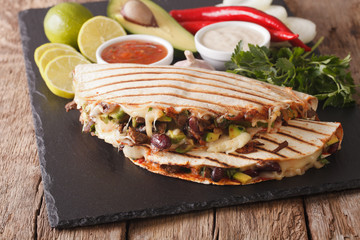 quesadilla with minced beef, beans, avocado and cheese close-up. horizontal