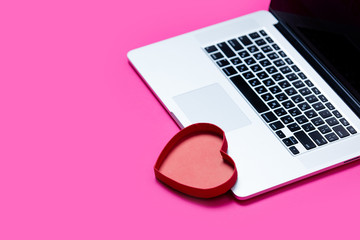 beautiful heart shaped toy and cool laptop on the wonderful pink background