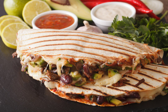 Mexican food: Quesadillas with beef, beans, avocado and cheese close-up. horizontal