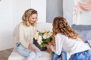 Daughters giving their mother a present and flowers