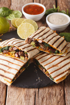Mexican quesadilla with ground beef, spinach and cheddar cheese close-up. vertical
