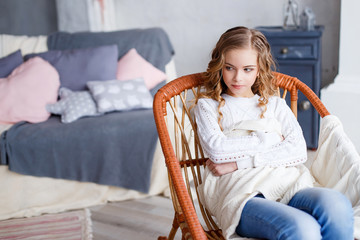 A thoughtful young girl sitting in an rocking chair in front of the fireplace